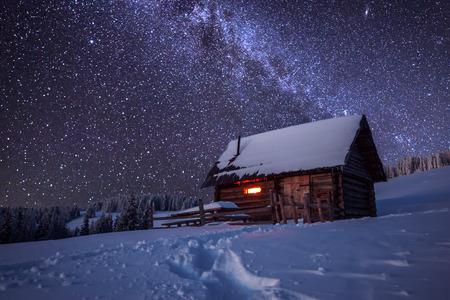 montañas nevadas: casa de madera en el bosque de invierno