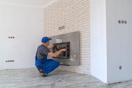 Fireplace installing in white brick wall Stockfoto