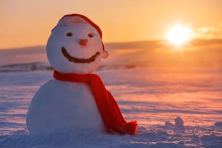 christmas winter: snowman on orange sunset background Stock Photo