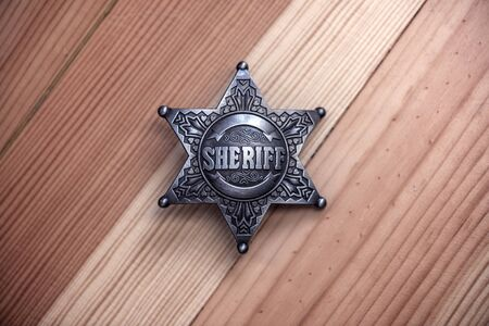 metal sheriff star on wood background