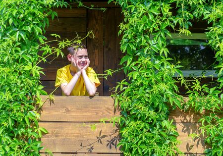 green building: Smiling boy on treehouse. Summer time!