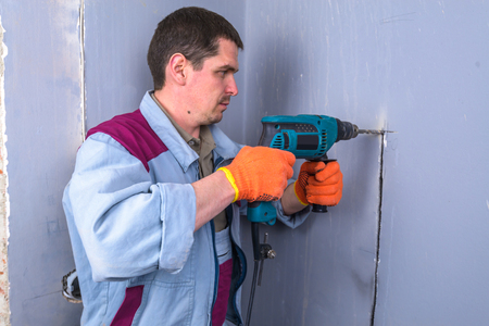 drills: worker drills a wall in house