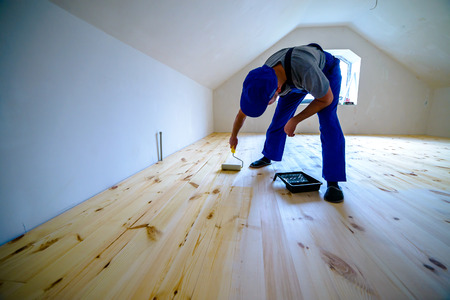 wood floor: Wooden floor varnished. Worker with paint roller.