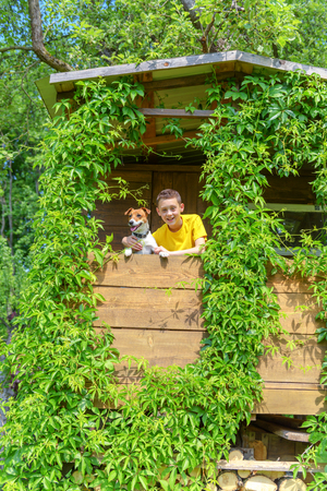 green building: Smiling boy with dog on treehouse. Summer time!