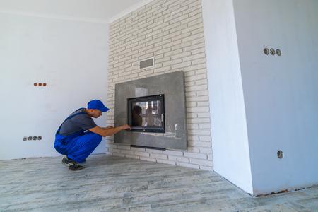mantelpiece: Fireplace installing in white brick wall Stock Photo