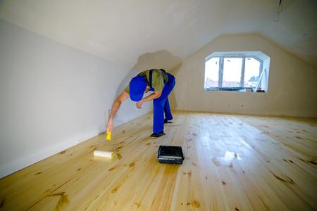 varnished: Wooden floor varnished. Worker with paint roller.