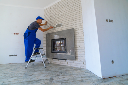 Fireplace installing in white brick wall Stock Photo