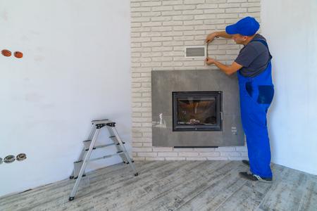 firebox: Fireplace installing in white brick wall Stock Photo
