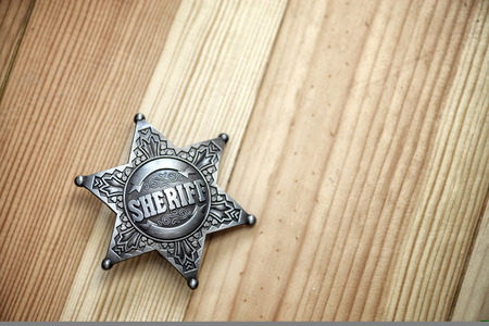 sheriff star on wood table closeup Stock Photo