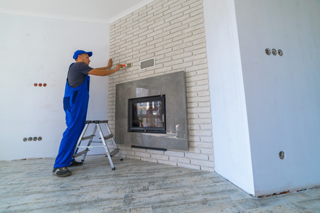 firebox: Man on Fireplace installing in white brick wall