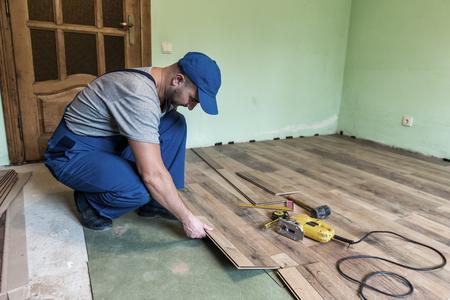 Arbeiter installieren Sie den Laminatfußboden photo