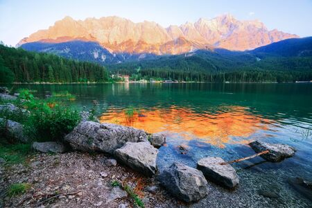Fantastic sundown on mountain lake Eibsee, located in the Bavaria, Germany. Dramatic unusual scene. Alps, Europe. Stock Photo