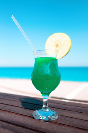 Green cocktail with apple piece on wooden table. Sunny day near mediterranean sea. Summer time