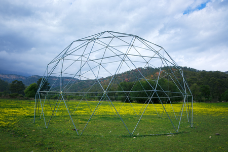 celling: Globe celling metal construction on blue sky background. Exterior of agriculture greenhouse in eco region