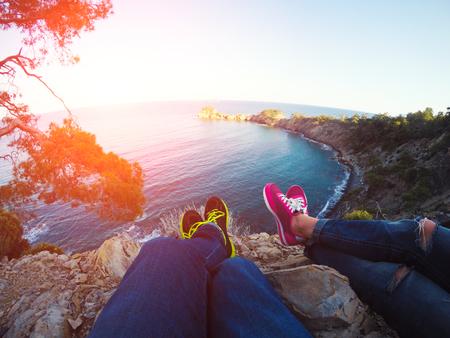 Paar Beine hängen über Felsen und Seebucht. Erstaunliche Szene auf Mittelmeer Seacost, Sommerzeit photo