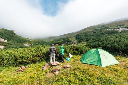 Ein paar Touristen in der Nähe von ihnen Zelt vor dem Hintergrund einer unglaublichen Berglandschaft. Sonniger Tag im Hochland photo