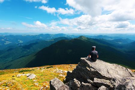 Ein einsamer Tourist, der am Rande der Klippe vor dem Hintergrund einer unglaublichen Berglandschaft sitzt. Sonniger Tag und blauer Himmel photo