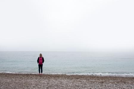 Allein Mädchen bleiben in der Nähe von Meer. Bewölkter Himmel und nebliges Wasser