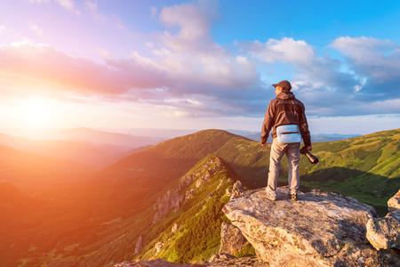 Ein einsamer Tourist, der am Rande der Klippe vor dem Hintergrund einer unglaublichen Berglandschaft liegt. Sonniger Tag und blauer Himmel photo