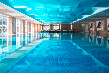 Indor swimming pool with blue wavy roof. Clear water and calm surface Lizenzfreie Bilder