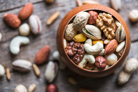 Dried mixed nuts in wooden bowl closeup. Walnut, pistachio, hazelnut, almond and other. Studio macro shoot.
