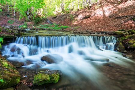 Erstaunliche Wasserfall Kaskaden im Frühjahr Wald. Blaue Ströme von fließendem Wasser