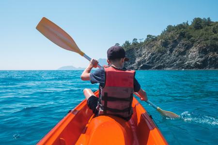 Junge in Rettungsweste auf orange Kajak. Sonniger Tag auf dem Mittelmeer. Sommerzeit