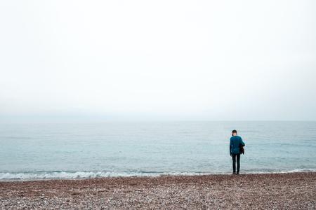 Alleiniger Junge bleibt in der Nähe von Meer. Bewölkter Himmel und nebliges Wasser Lizenzfreie Bilder