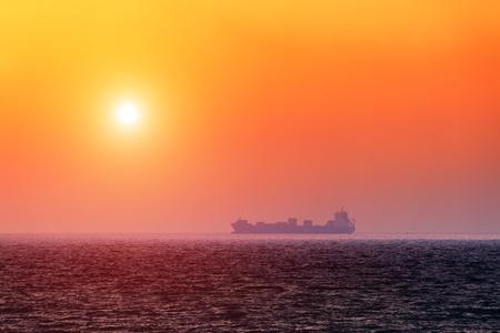 Allein Lastkahn in ruhigem Meer. Orange Himmel glühend durch Sonnenlicht Lizenzfreie Bilder
