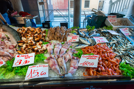 Seafood market with price list. Fresh fish, shrimp, crab and squid on ice
