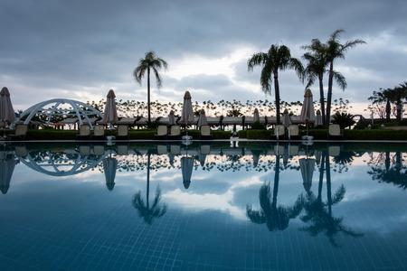 Schwimmbad mit Sonnenschirmen und Liegestuhl in der Morgenzeit. Erstaunliche Szene in der Nähe des Mittelmeeres Lizenzfreie Bilder