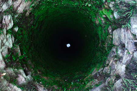 Terrible old deep well with moss. Luminous circle on the bottom
