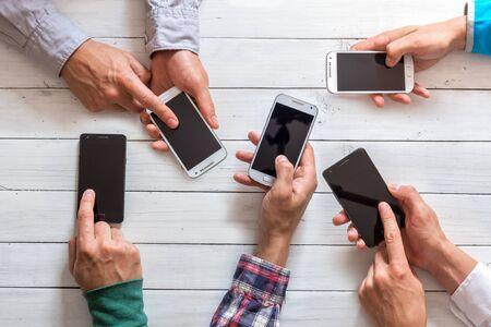 Mobiltelefone in Freunden Hand Großansicht. Netzwerksüchtiges Konzept Lizenzfreie Bilder