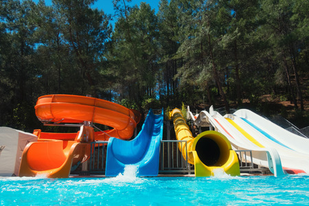 Colorful aquapark in green forest. Summer attraction in sea resort