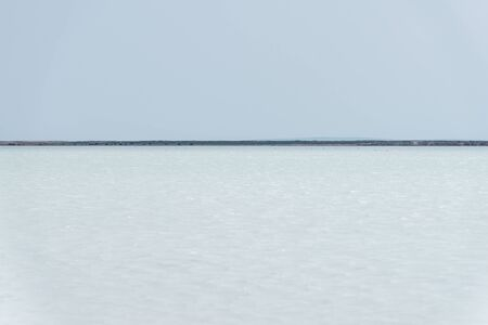 A minimalistic scene with a clear sky, blue water and a horizon line