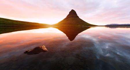 Colorful sunrise on Kirkjufellsfoss waterfall. Amazing morning scene near Kirkjufell volkano, Iceland, Europe. Lizenzfreie Bilder