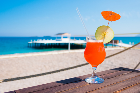 Orange Cocktail mit Apfelstück auf Holztisch. Sonniger Tag in der Nähe des Mittelmeeres. Sommerzeit