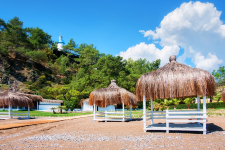 Sommerlaube am Strand. Atemberaubende Aussicht auf das Mittelmeer. Weiße hölzerne Sommerhäuser am sonnigen Tag. Blauer Himmel und flauschige Wolken