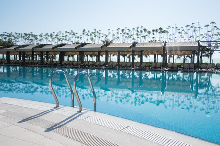Swimming pool with sunshades and lounge chair in morning time. Amazing scene near mediterranean sea Lizenzfreie Bilder