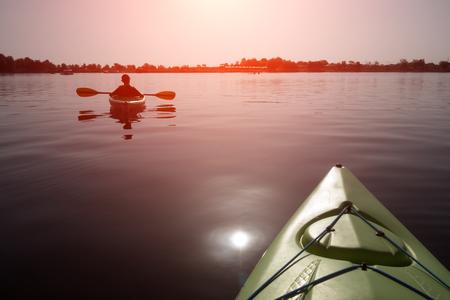 Boy in life jacket on green kayak Lizenzfreie Bilder