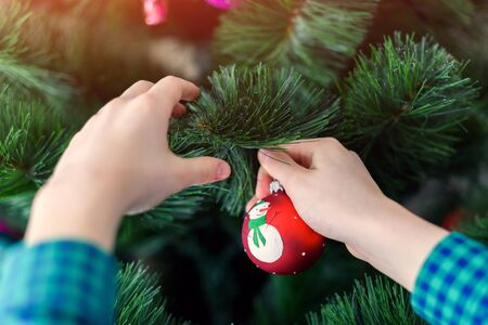Boy hangs a Christmas tree toy Stock Photo