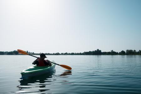 Boy in life jacket on green kayak Standard-Bild