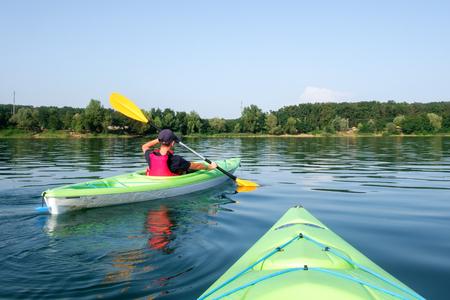 Boy in life jacket on green kayak. Sunny day on wonderful lake. Summer time Standard-Bild