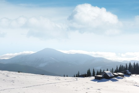 Fantastic landscape with snowy mountains, trees and house. Carpathian mountains, Ukraine, Europe Stock Photo