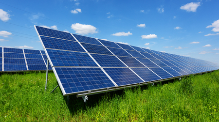 Solar panel on blue sky background. Green grass and cloudy sky. Alternative energy concept