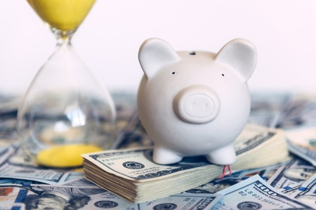 Piggy moneybox with dollar cash and sand clock closeup. Financial concept