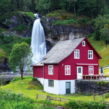 Red house near one of the most popular waterfalls in Norway - Steinsdalsfossen, on the Fosselva river in western Norway
