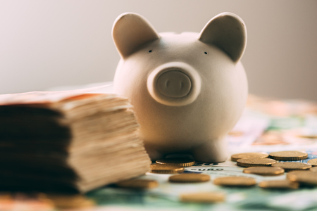 Piggy moneybox with euro cash and coins closeup. Financial concept