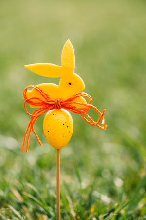 Easter background concept with yellow bunny figure and egg on wood stick in green grass Banque d'images