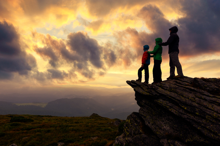 Family of tourists staying on the edge of the cliff against the backdrop of an incredible mountain landscape. Evening time and orange sunset